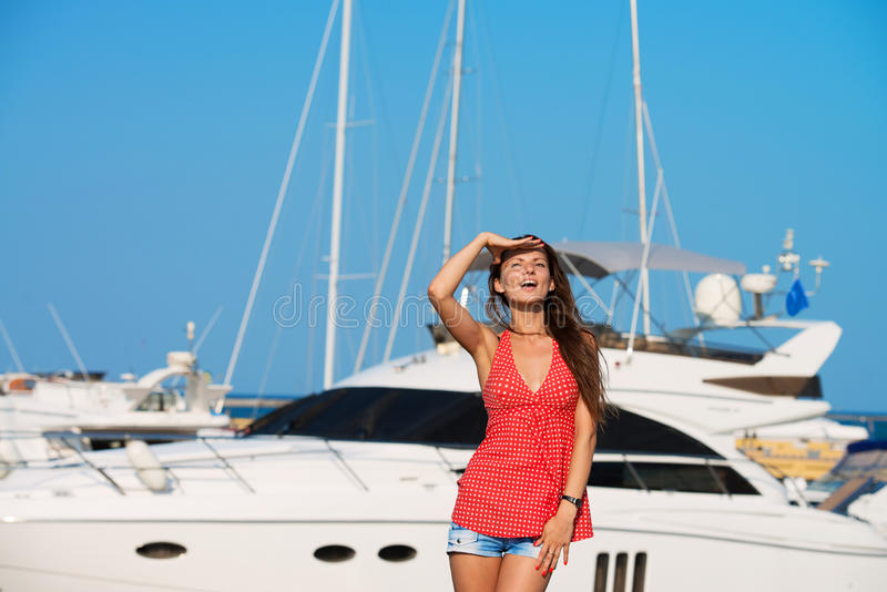 Pretty girl at the yacht harbor stock photo