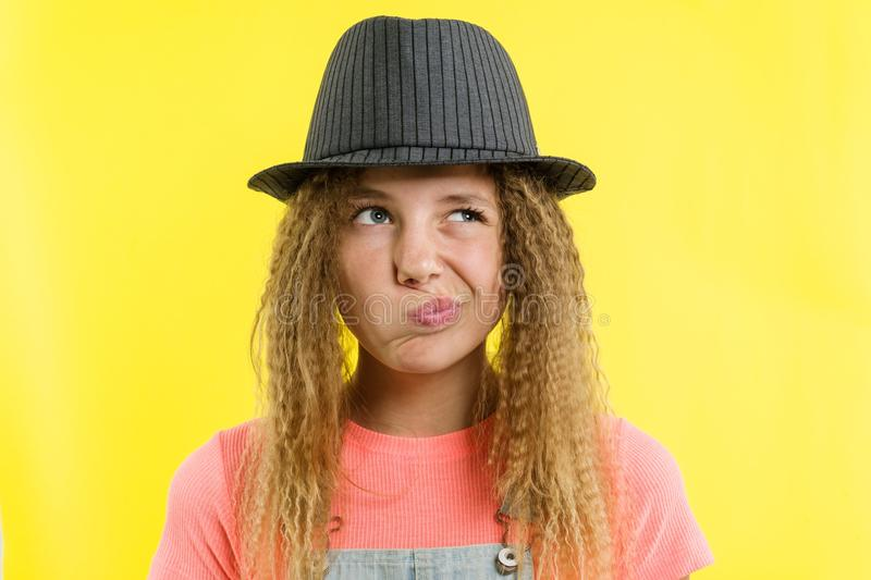 Pretty girl 12-13 years old blonde with curly hair in a hat, looks pensively aside, thinking about school. royalty free stock photo