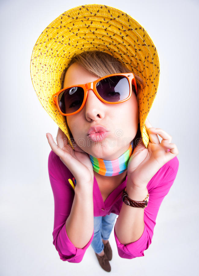 Pretty girl with yellow summer hat giving a kiss royalty free stock photography