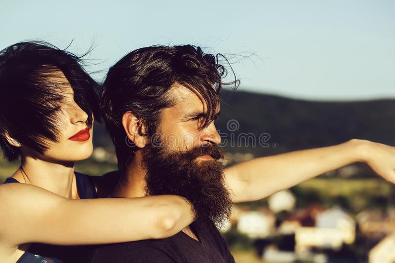 Pretty girl hugs handsome man. Pretty girl young beautiful women with red lips and short brunette hair hugs handsome men hipster with long beard and moustache on stock photography
