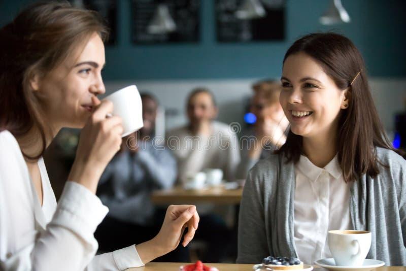 Pretty girls having fun in cafe drinking coffee royalty free stock photo