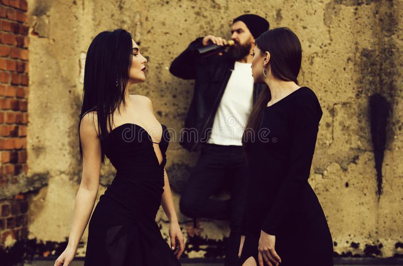 Pretty girls watching brutal man with beard drinking wine. Pretty girls with long, brunette hair in fashion, black dresses watching brutal men with beard royalty free stock image