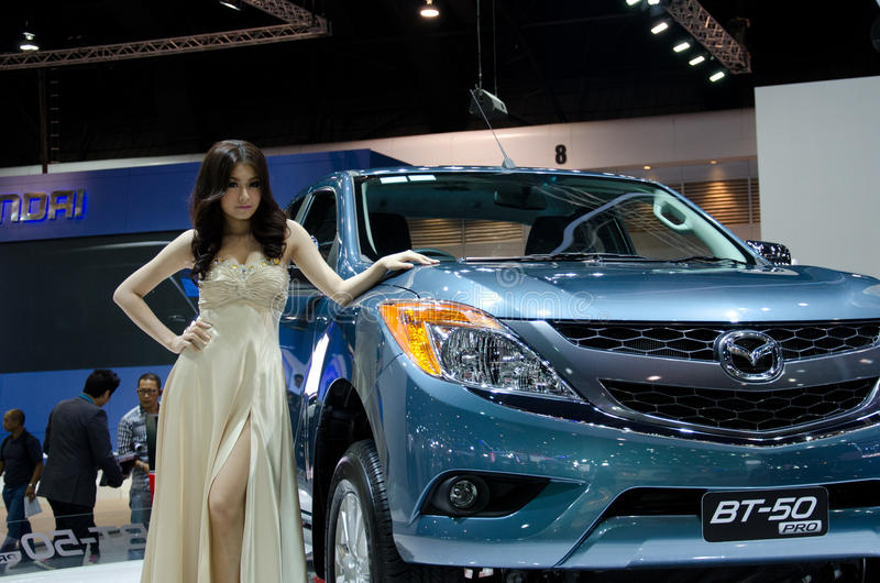 Pretty girls with Mazda. BANGKOK - DECEMBER 3: Mazda BT-50 car with unidentified model on display at the 28th Thailand International Motor Expo on December 3 stock photos