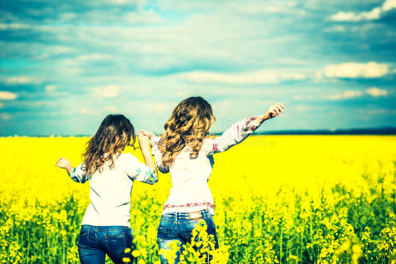 Pretty girls running in the field in embroidery shirts royalty free stock photography