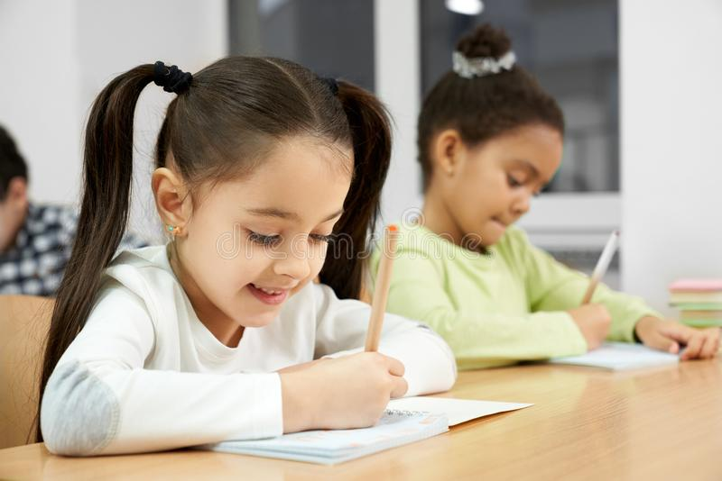 Pretty girls sitting at desk in class, writing in copybook. stock photo