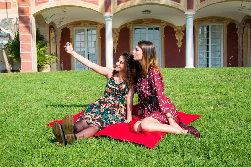 Pretty girls are taking a selfie with a smartphone. Two cute girls are taking a selfie with their smartphone. They are dressed with colorful dresses and sitting stock images