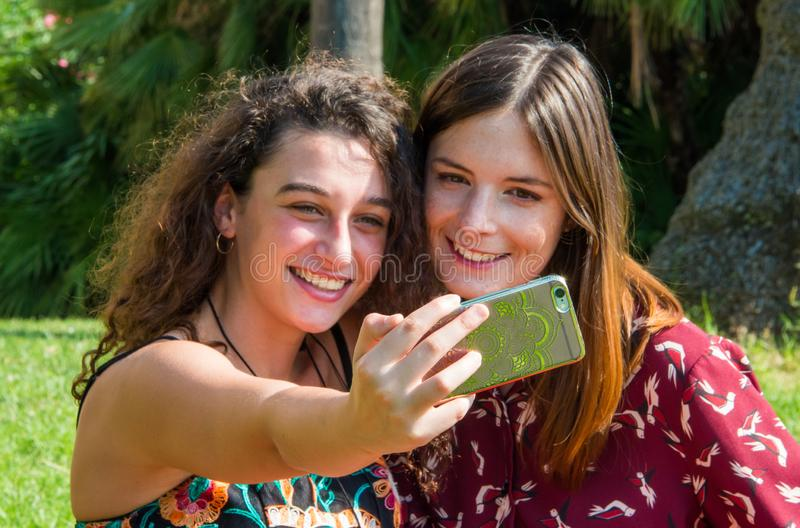 Pretty girls are taking a selfie with a smartphone. Two cute girls are taking a selfie with their smartphone. They are dressed with colorful dresses and sitting royalty free stock image