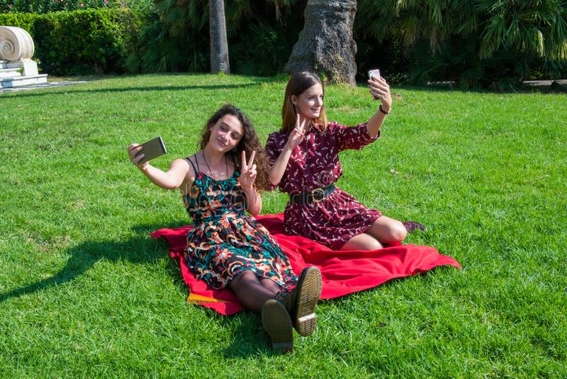 Pretty girls are taking a selfie with a smartphone. Two cute girls are taking a selfie with their smartphone. Showing the piece sign. They are dressed with royalty free stock photos