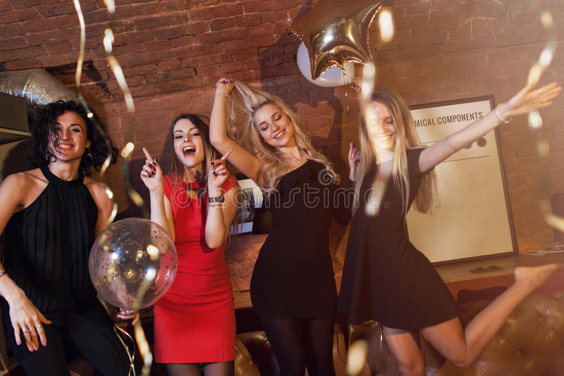 Pretty girls wearing cocktail dresses having birthday party fooling around dancing in nightclub royalty free stock image