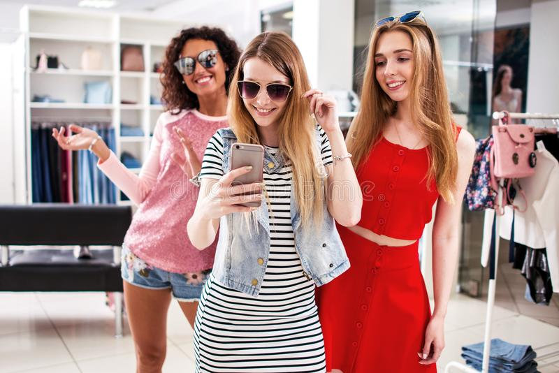 Pretty girls wearing sunglasses fooling around taking selfie showing tongue and horn gestures in clothing shop.  stock photo