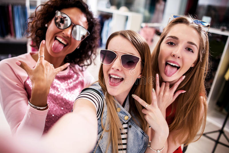 Pretty girls wearing sunglasses fooling around taking selfie showing tongue and horn gestures in clothing shop royalty free stock photos