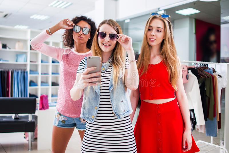 Pretty girls wearing sunglasses fooling around taking selfie showing tongue and horn gestures in clothing shop.  royalty free stock photos