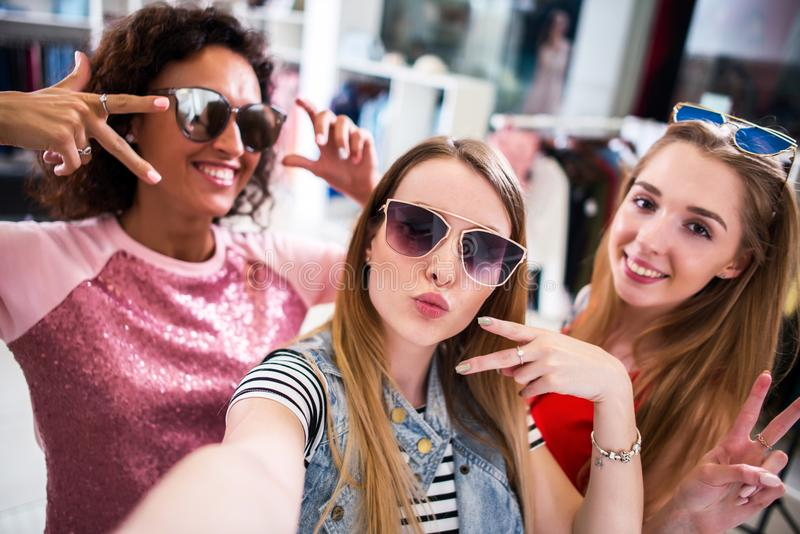 Pretty girls wearing sunglasses fooling around taking selfie showing tongue and horn gestures in clothing shop.  stock photography