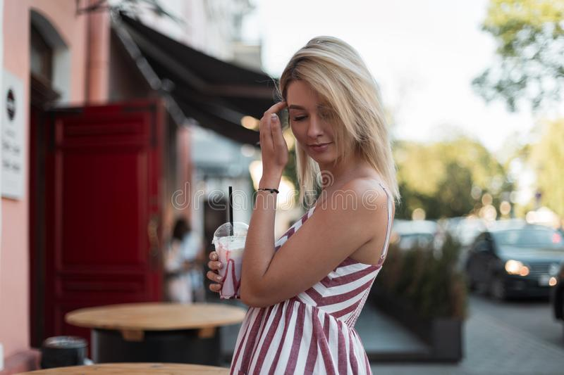 Pretty glamorous young blond woman in a fashionable pink striped dress with a sweet milk drink poses near a open cafe in the city. Modern cute girl model royalty free stock photo
