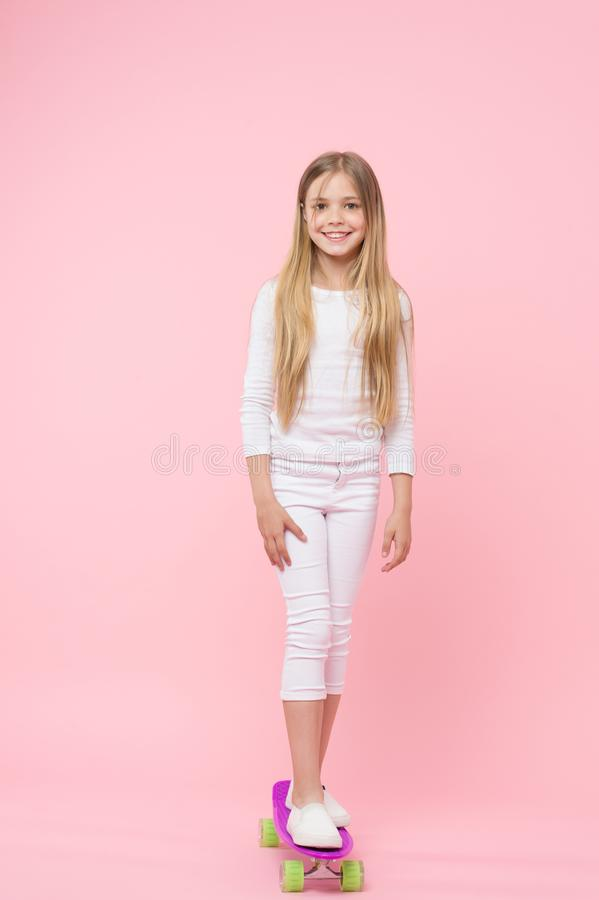 A pretty good skater girl. Cute small girl standing on skateboard on pink background. Little girl child on violet penny royalty free stock photo