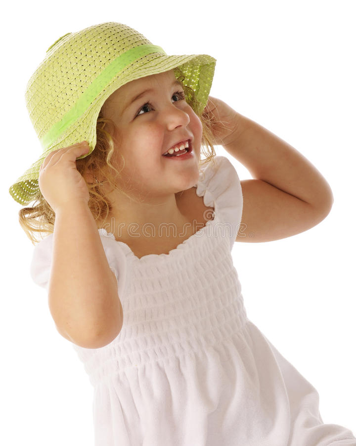 Pretty with Green Easter Bonnet. Portrait of a beautiful preschooler trying on a spring green Easter bonnet stock photography