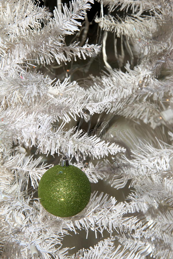 Pretty green ornament hanging from white Christmas tree royalty free stock images