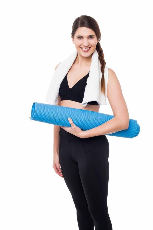 Pretty gym woman holding blue mat royalty free stock photo