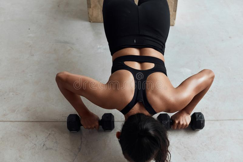 Pretty gym woman push-up dumbbells in gym. Top view on muscular female during push ups with dumbbells. Bodybuilding royalty free stock photography