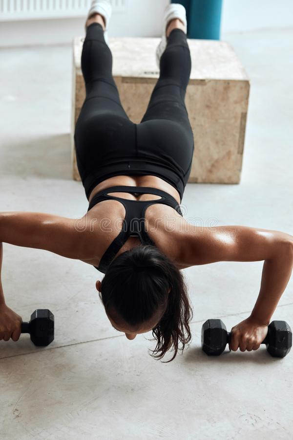 Pretty gym woman push-up dumbbells in gym. Top view on muscular female during push ups with dumbbells. Bodybuilding stock photo