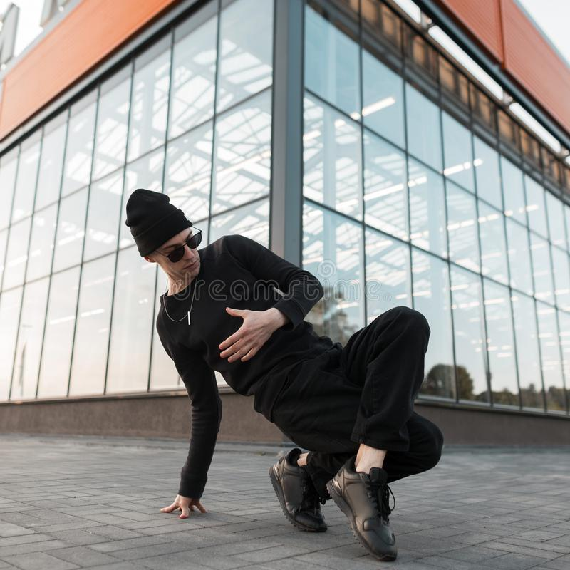 Pretty handsome young hipster man dancer in knitted hat in stylish black clothes in trendy sunglasses dancing break dance. In the city near the glass building royalty free stock photos