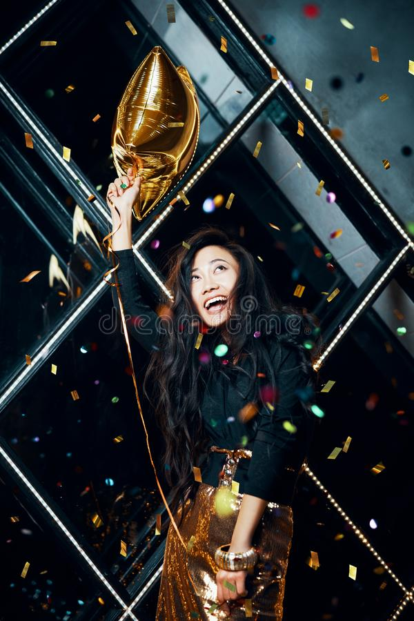 Pretty happy asian woman having fun and dancing at party holding golden balloon royalty free stock photos