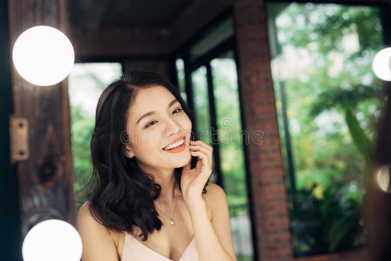 Pretty happy asian woman watching on herself in a big mirror at royalty free stock photography