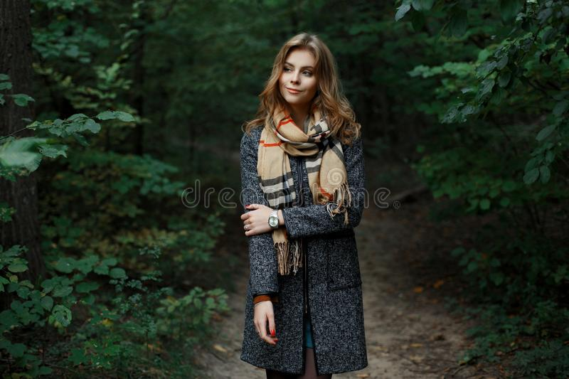 Pretty happy beautiful European young woman in a vintage checkered scarf in a fashionable gray coat walks in the woods royalty free stock photo