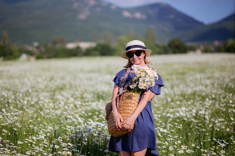 Beautiful woman with basket of flowers over chamomile field. Carefree happy brunette woman in straw hat in blue dress. royalty free stock photo