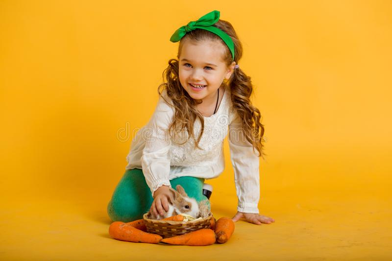 Pretty happy child girl with carrots and her friend little colorful rabbit, Easter holiday concept isolated on yellow. Beautiful happy little child girl on royalty free stock photography
