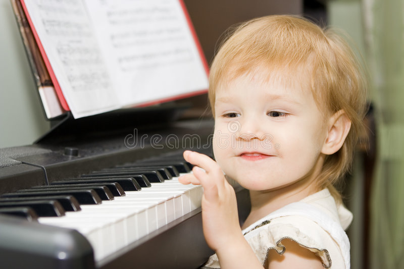 Pretty happy child play piano royalty free stock images