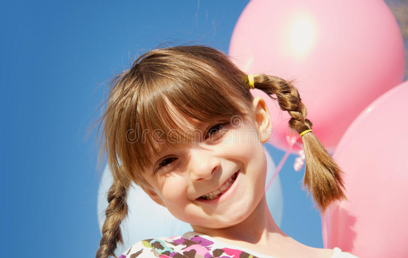 Pretty happy little girl holding balloons. Against blue sky background stock images