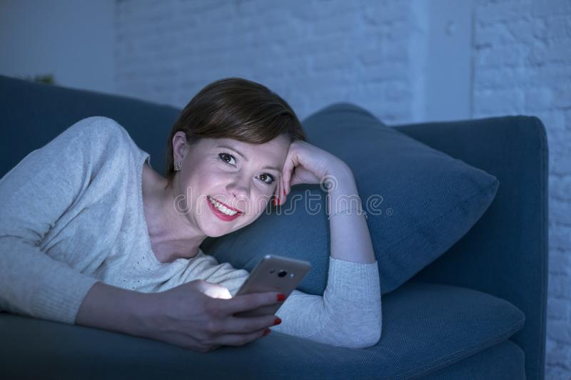 Pretty and happy red hair woman on her 20s or 30s lying on home couch or bed using mobile phone late at night smiling in internet. Young pretty and happy red royalty free stock images