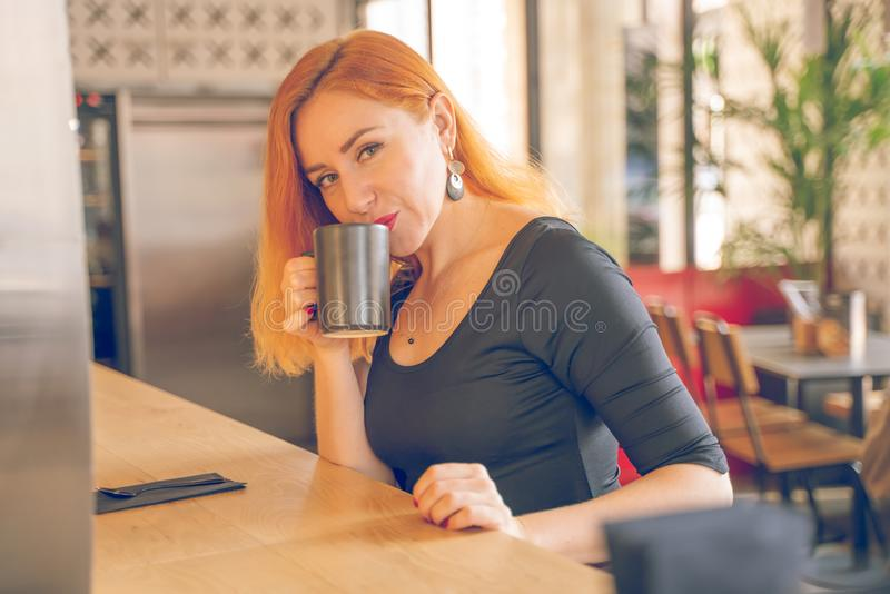 Pretty happy redheaded caucasian woman in black shirt drinks cup of coffee in the modern cafe alone royalty free stock photos
