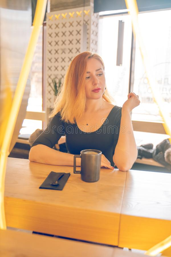 Pretty happy redheaded caucasian woman in black shirt drinks cup of coffee in the modern cafe alone stock photography