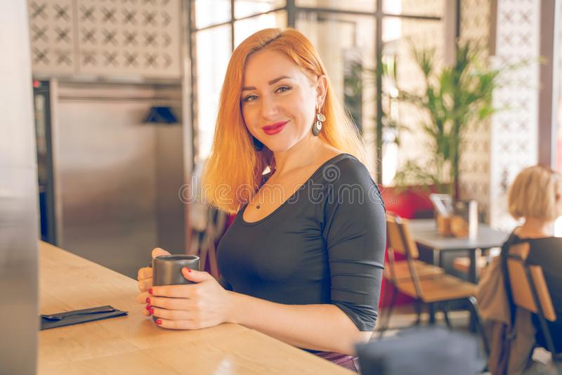 Pretty happy redheaded caucasian woman in black shirt drinks cup of coffee in the modern cafe alone royalty free stock image