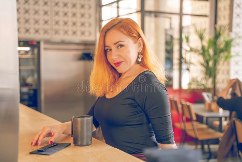 Pretty happy redheaded caucasian woman in black shirt drinks cup of coffee in the modern cafe alone royalty free stock images