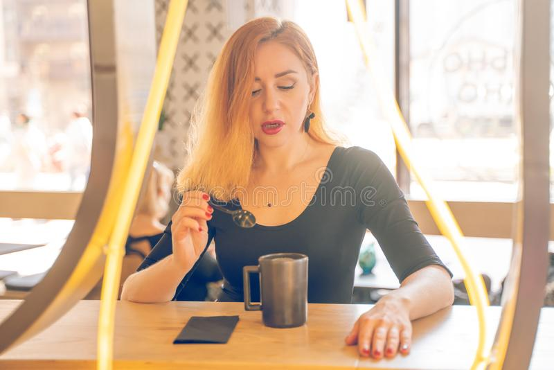Pretty happy redheaded caucasian woman in black shirt drinks cup of coffee in the modern cafe alone stock photos