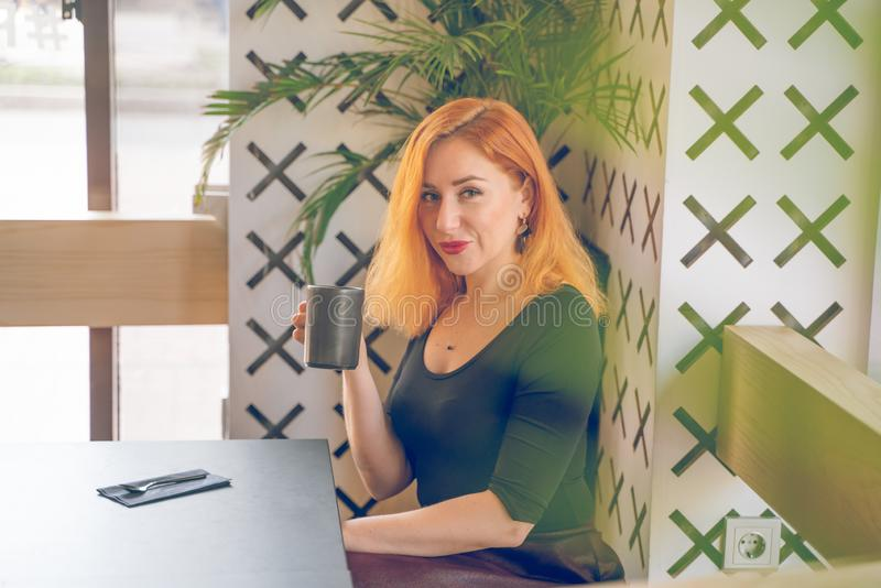 Pretty happy redheaded caucasian woman in black shirt drinks cup of coffee in the modern cafe alone royalty free stock photography