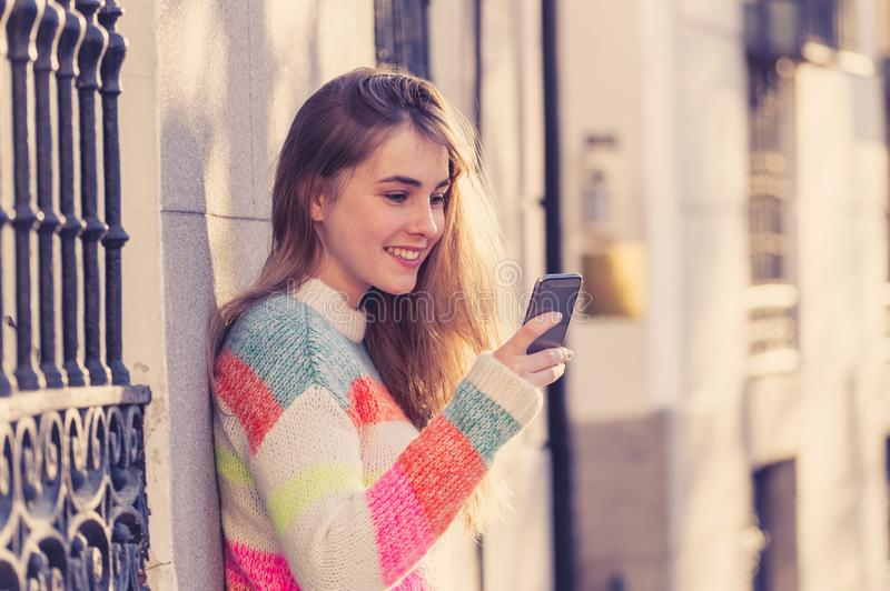 Attractive young woman on smart phone checking social media mobile apps outside city royalty free stock photos
