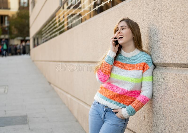Attractive young teenager woman talking and chatting on her smart phone outside in an European city stock photos