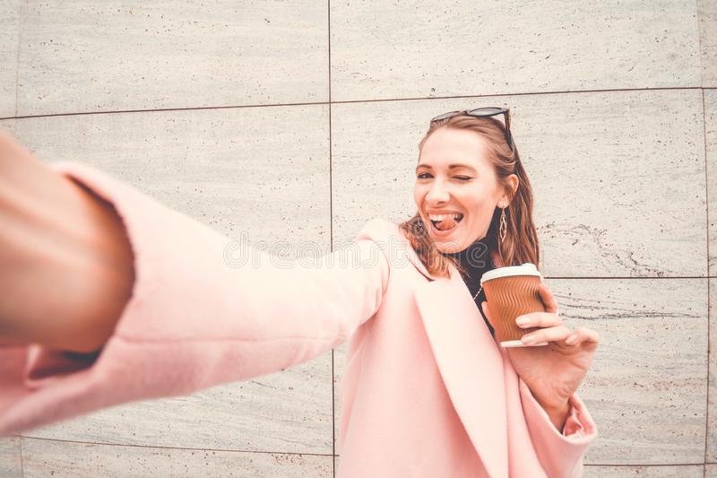 Pretty and happy woman having fun and taking selfie with sticking out tongue. She holds a coffee cup in left hand and smartphone t royalty free stock photography