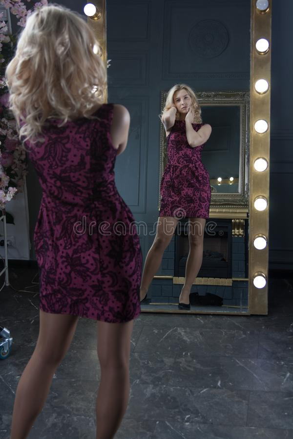 pretty happy woman watching on herself in a big mirror. The girl chooses an dress for the holiday. Vertical full length rearview royalty free stock photography