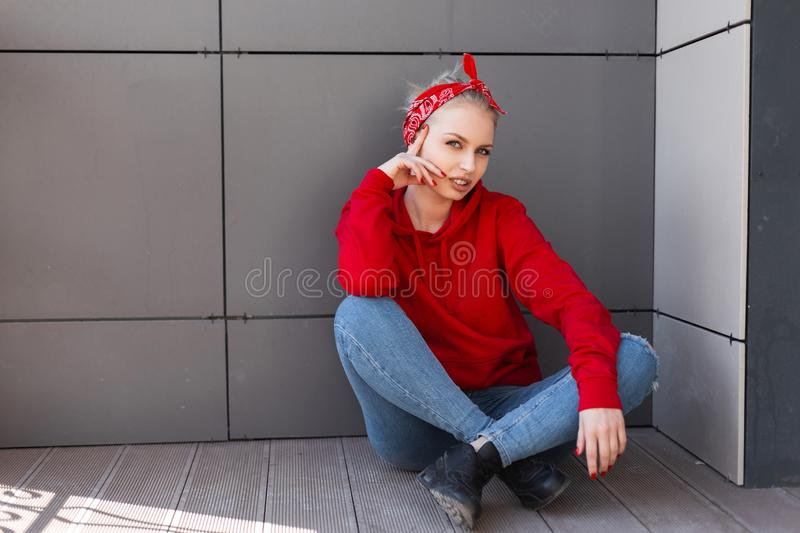Pretty happy young blond woman in a stylish bandana with a pattern in blue jeans in a fashionable red sweatshirt in black boots. Resting sitting near a gray royalty free stock photography