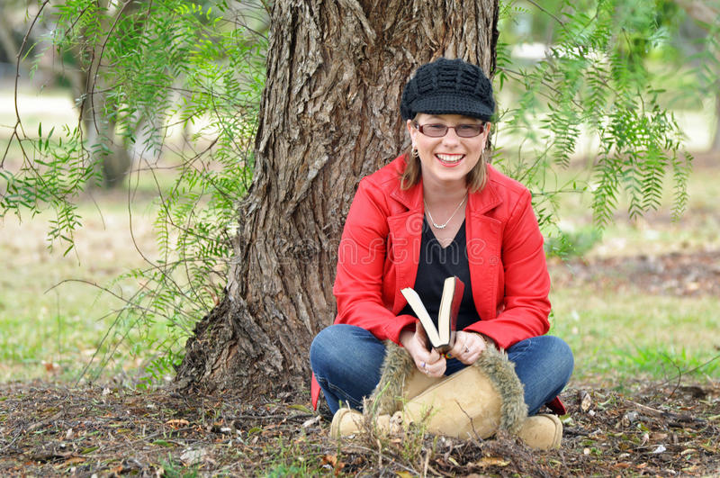 Pretty happy young woman laughing outdoors under tree. A beautiful young lady sitting under a huge old weeping willow tree outdoor in a park. The young woman is royalty free stock photo