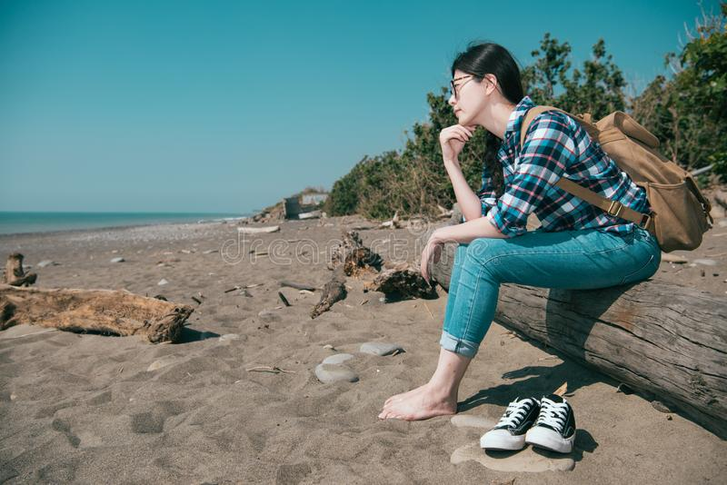 Pretty hiker take off shoes sitting on wooden. Pretty elegant female hiker take off shoes sitting on wooden and looking at distance thinking daydreaming viewing royalty free stock photo