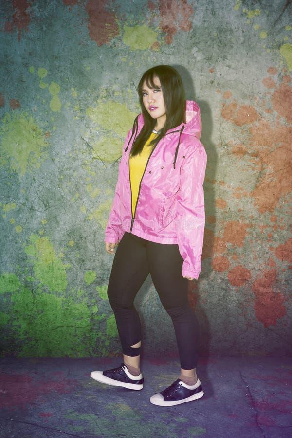 Pretty hip hop dancer looks confident on studio stock photos