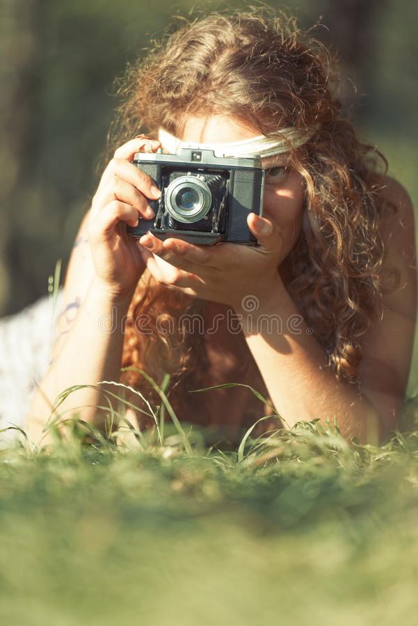 Pretty hippie girl on the grass taking photos with an old camera. Outdoor in peace and free love. Top view - Vintage effect photo royalty free stock photos