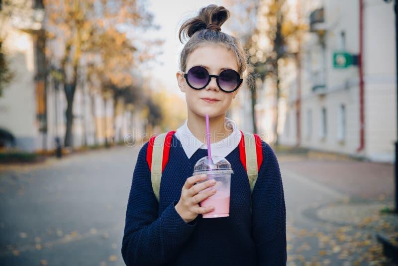 Pretty hipster teen with red bag drinks milkshake from a plastic cup walking street between buildings. Cute girl in stock photos