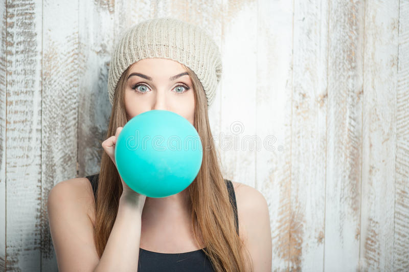 Pretty hipster woman is inflating colored balloon. Waist up portrait of cheerful hipster girl with Caucasian appearance, who is standing near the white wall and stock image